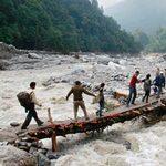 救援者在北阿坎德邦協助人們度過洪水氾濫的河流。(節錄自路透社新聞照)