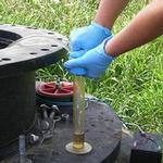 從一處營運中掩埋場的人孔接入點蒐集垃圾滲出水樣本。(圖:Dana Kolpin、USGS。)