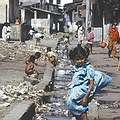 位於印度孟買的貧民窟,一位小女孩站在污水下水道前凝望著。圖片來源:Foreign Affairs and International Trade, Canada