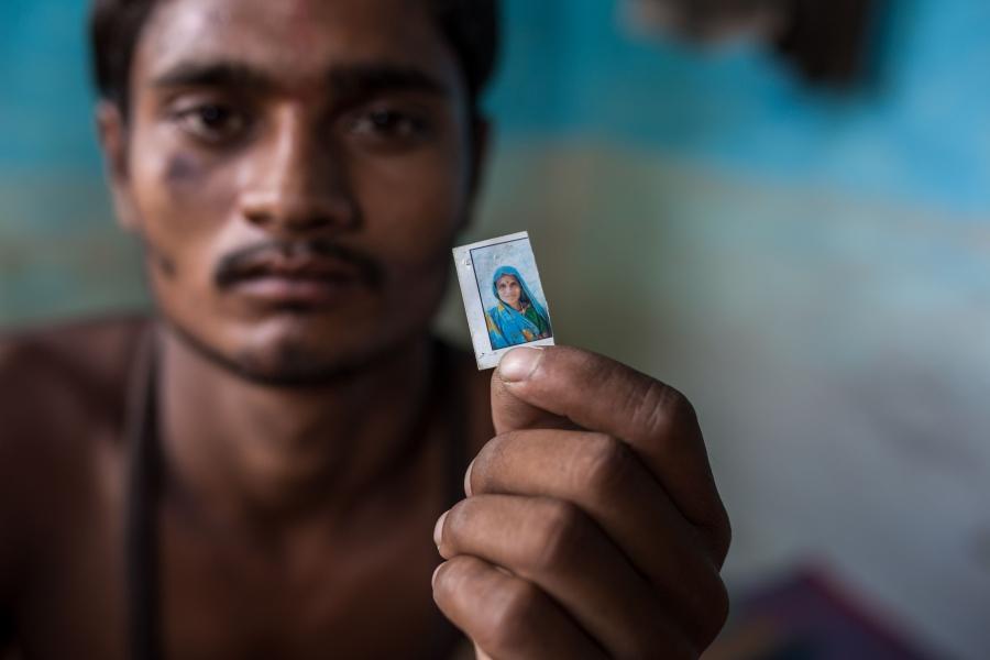 18歲的移工Pawan Singh悲傷地握著母親的照片。45歲的Suraj Singh與40歲的妻子Chandabai和兒子Pawan Singh在古爾岡的一家牛奶廠工作。每天的總收入為12美元,是村里收入的三倍。3月22日封城後一個月,他們的生活遭遇巨變。一家人決定帶著80美元的積蓄回到中央邦。在距家62英里處搭上一輛貨車的便車,但隨後發生車禍,Chandabai遭撞死。這家人把他們的玉米田拿去貸款,打點了Chandabai的火化費用和其他人的醫藥費。如今他們背負1300美元的債務,不知道如何還清。攝影:UNDP India / Dhiraj Singh