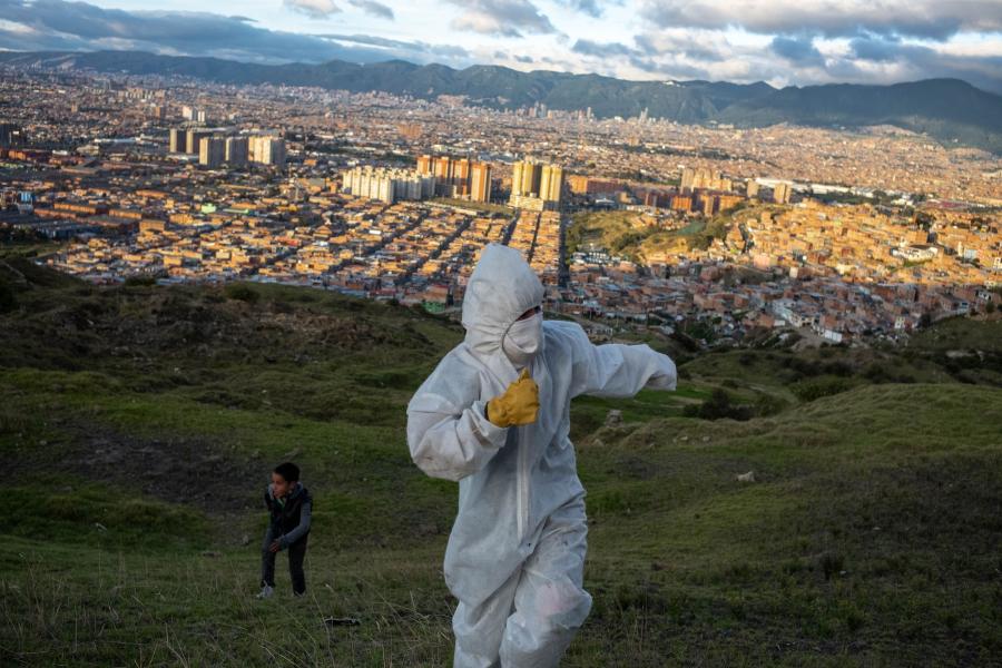 穿著全套防護裝備的抗議人士與孩子們一起玩耍。他們試圖阻止Los Altos de la Estancia貧民窟的拆除。 這邊許多居民都是非法勞工,因為疫情大流行而慘遭失業。(哥倫比亞,波哥大,2020年5月)。攝影: NadègeMazars