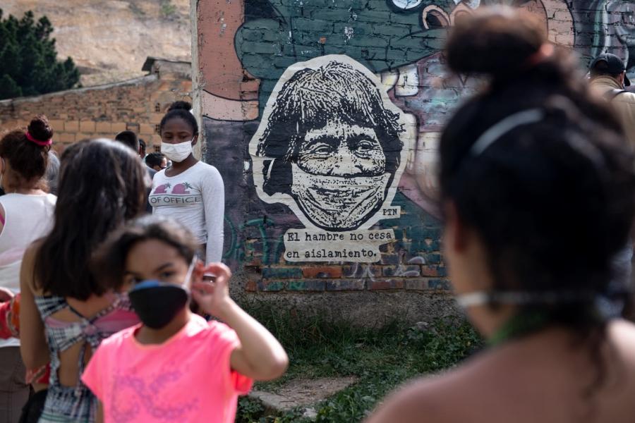 在工人階級城市玻利瓦爾城,受到疫情打擊最嚴重的人們,正在廚房排隊領湯。壁畫上是一位戴著口罩的原住民男子,旁邊寫著:「疫情隔離期間,飢餓不會停止。」(哥倫比亞,波哥大,2020年5月)。 攝影: NadègeMazars