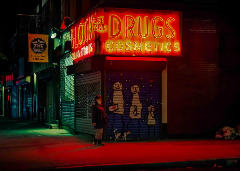 遛狗的人,閃著紅色霓虹燈的藥局招牌。(紐約市,東村。2020年5月)攝影:Dina Litovsky