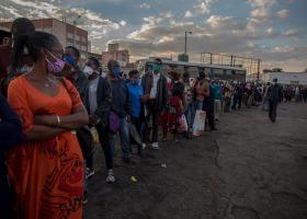 下班的人們,戴著口罩排隊準備搭乘大眾運輸工具回家。(辛巴威,哈拉雷,市集廣場巴士總站,2020年5月)。攝影: Cynthia Matonhodze